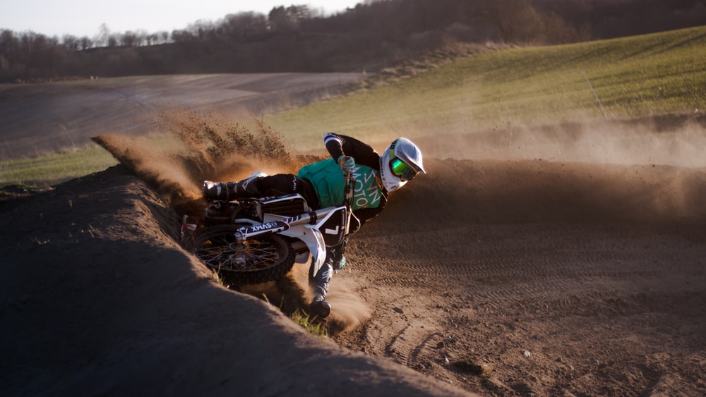 man riding motocross dirt bike on dirt road during daytime