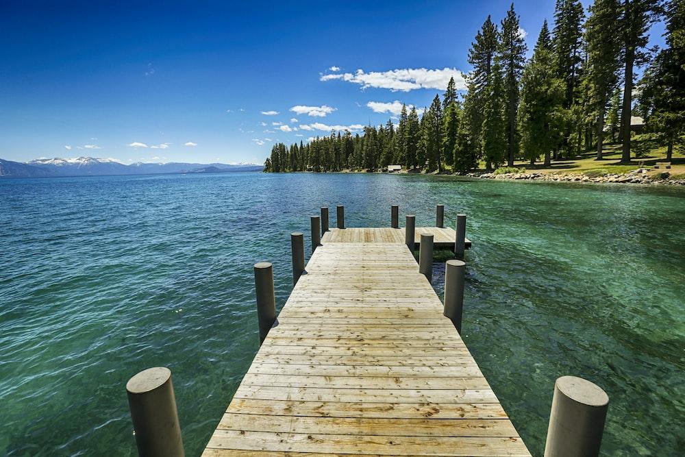 brown wooden dock on blue sea under blue sky during daytime