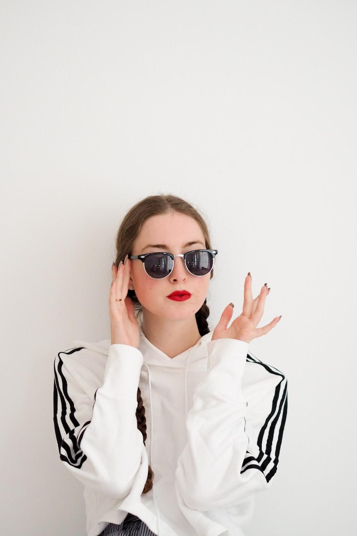 woman in white dress shirt wearing black framed sunglasses