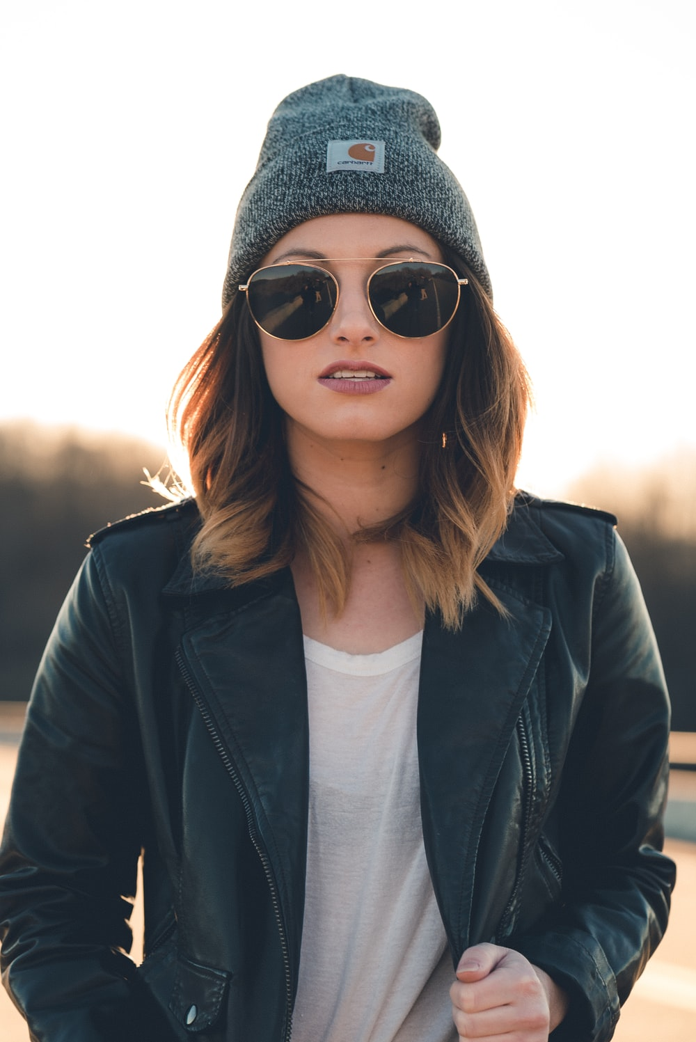 woman in black leather jacket wearing black sunglasses and gray knit cap