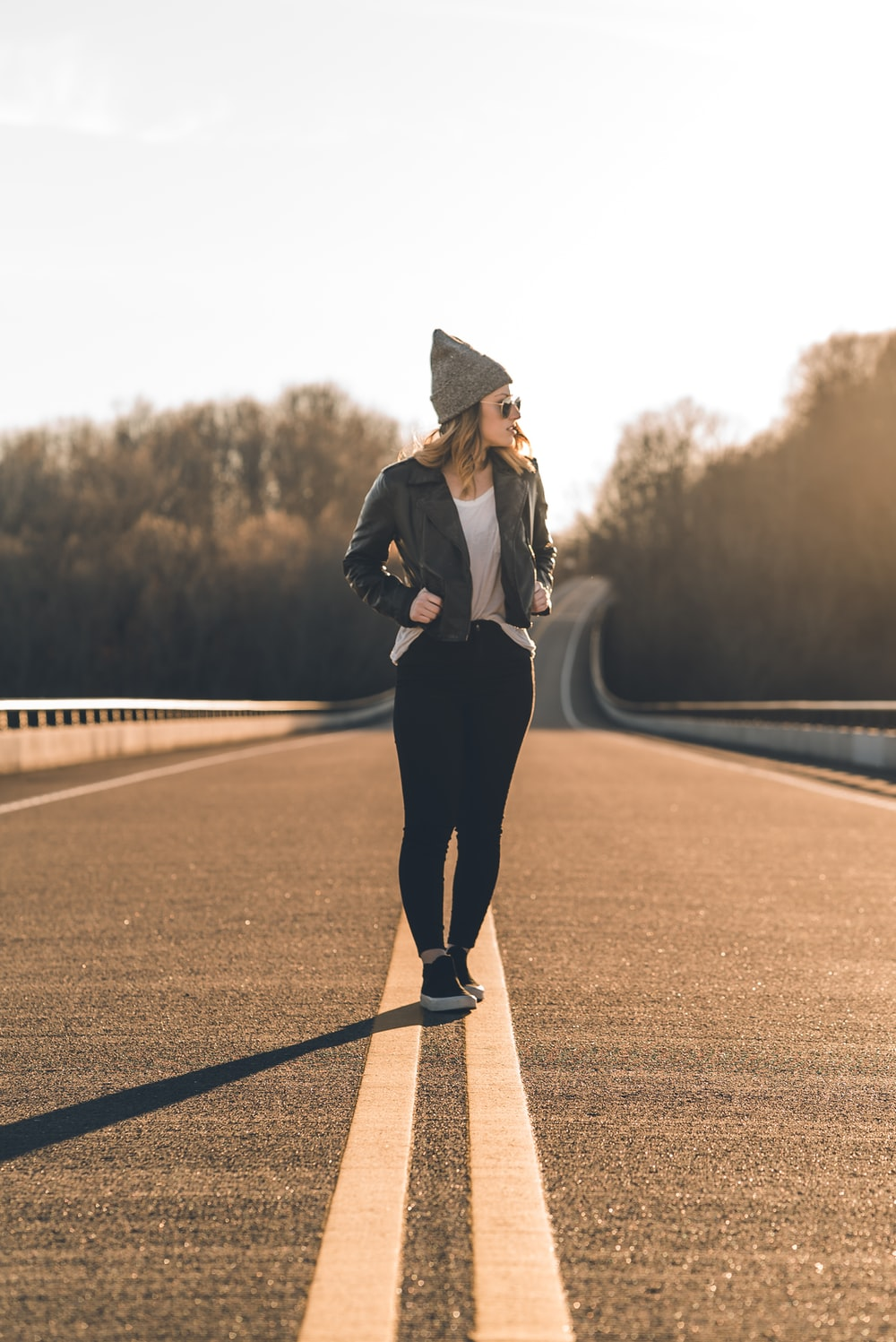 woman in black coat and black pants standing on road during daytime