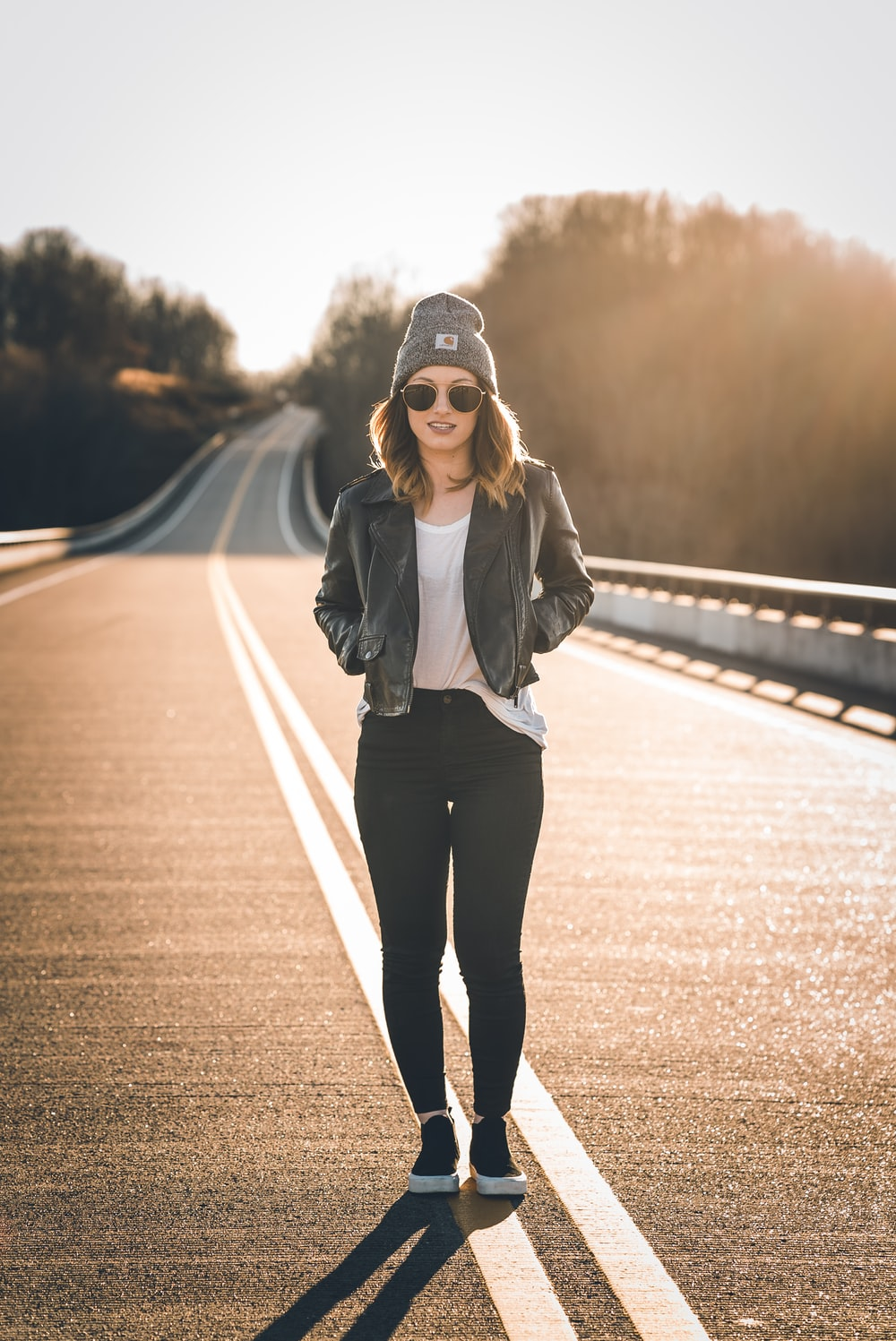 woman in black jacket and black pants standing on road during daytime