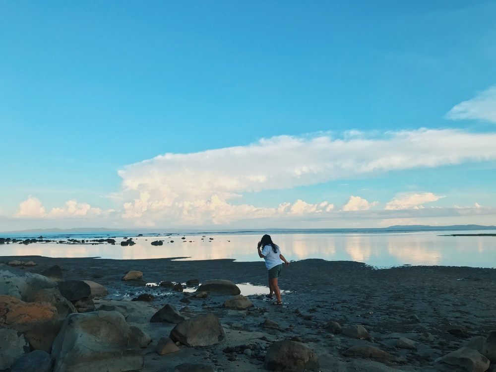 man in white t-shirt and black shorts standing on rocky shore during daytime