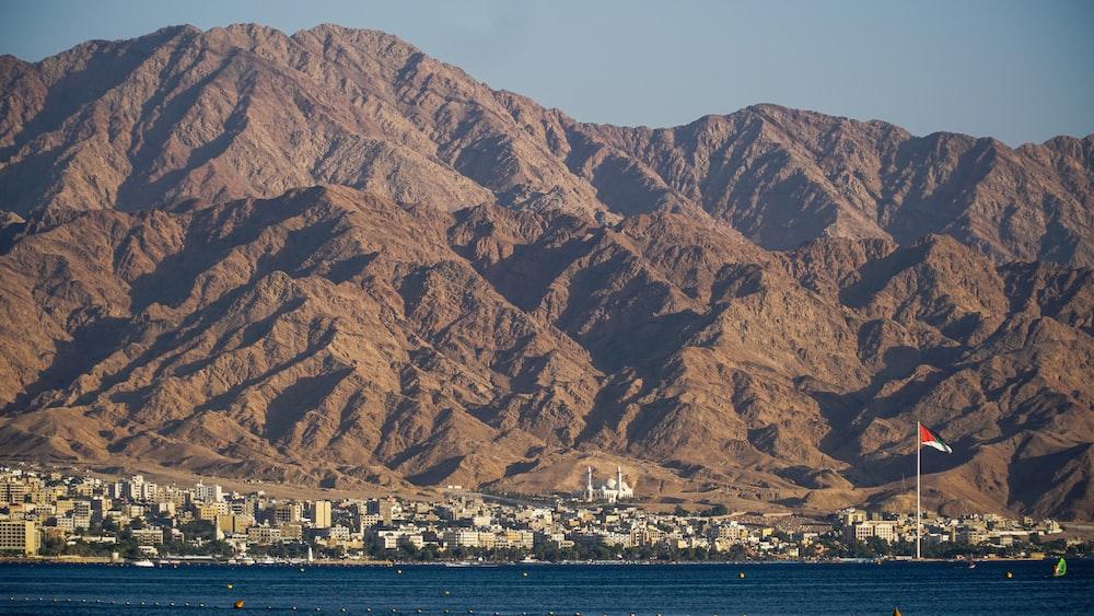 brown mountain near body of water during daytime