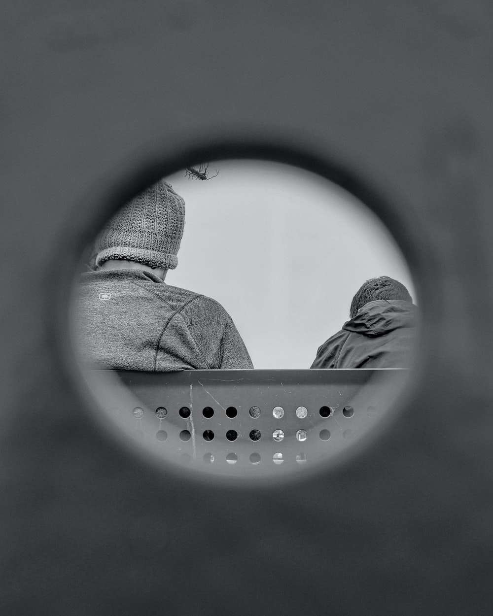 person in gray knit cap looking at round mirror