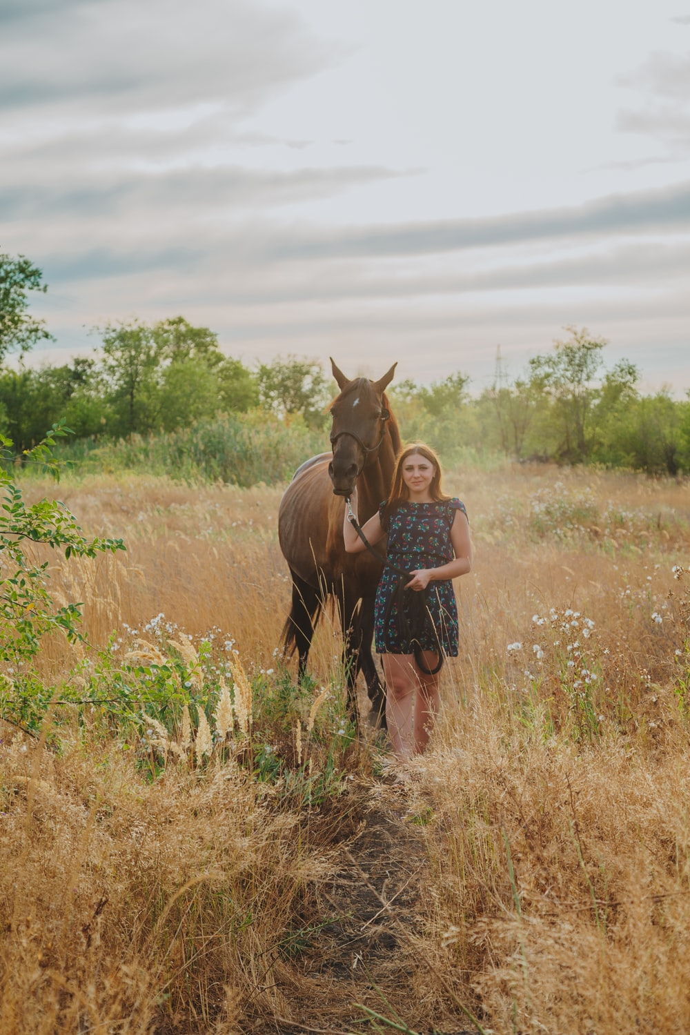 woman in red shirt standing beside brown horse during daytime