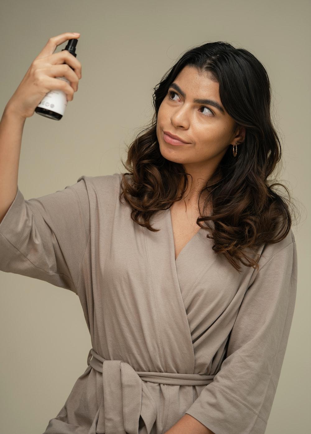woman in gray long sleeve shirt holding white bottle