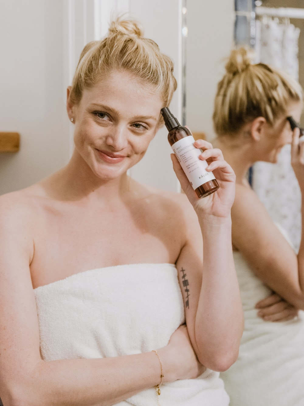 woman in white towel holding bottle