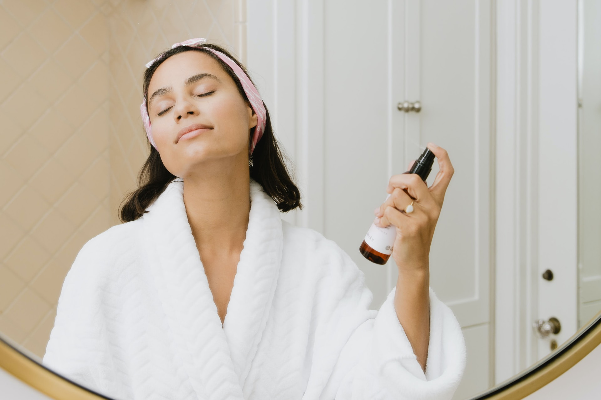 woman in white bathrobe holding smartphone