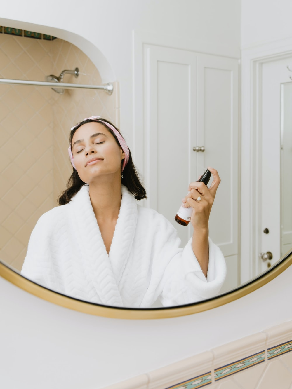 woman in white bathrobe holding smartphone