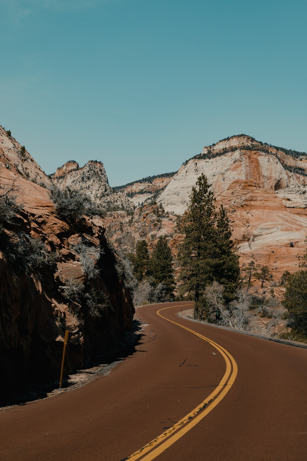gray asphalt road between brown rocky mountain during daytime