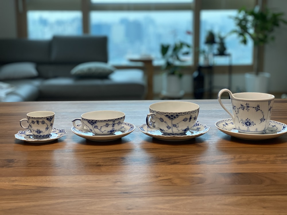 white and blue floral ceramic bowls on brown wooden table