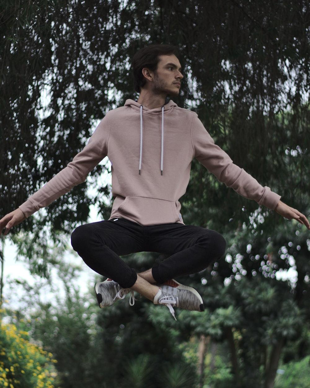 woman in pink hoodie jumping