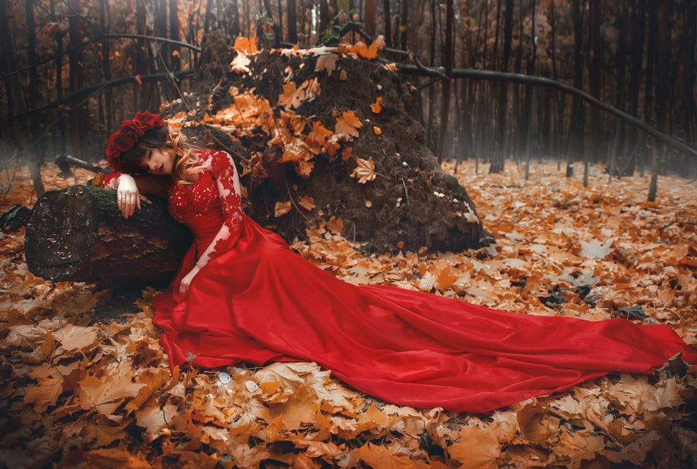 woman in red dress lying on dried leaves