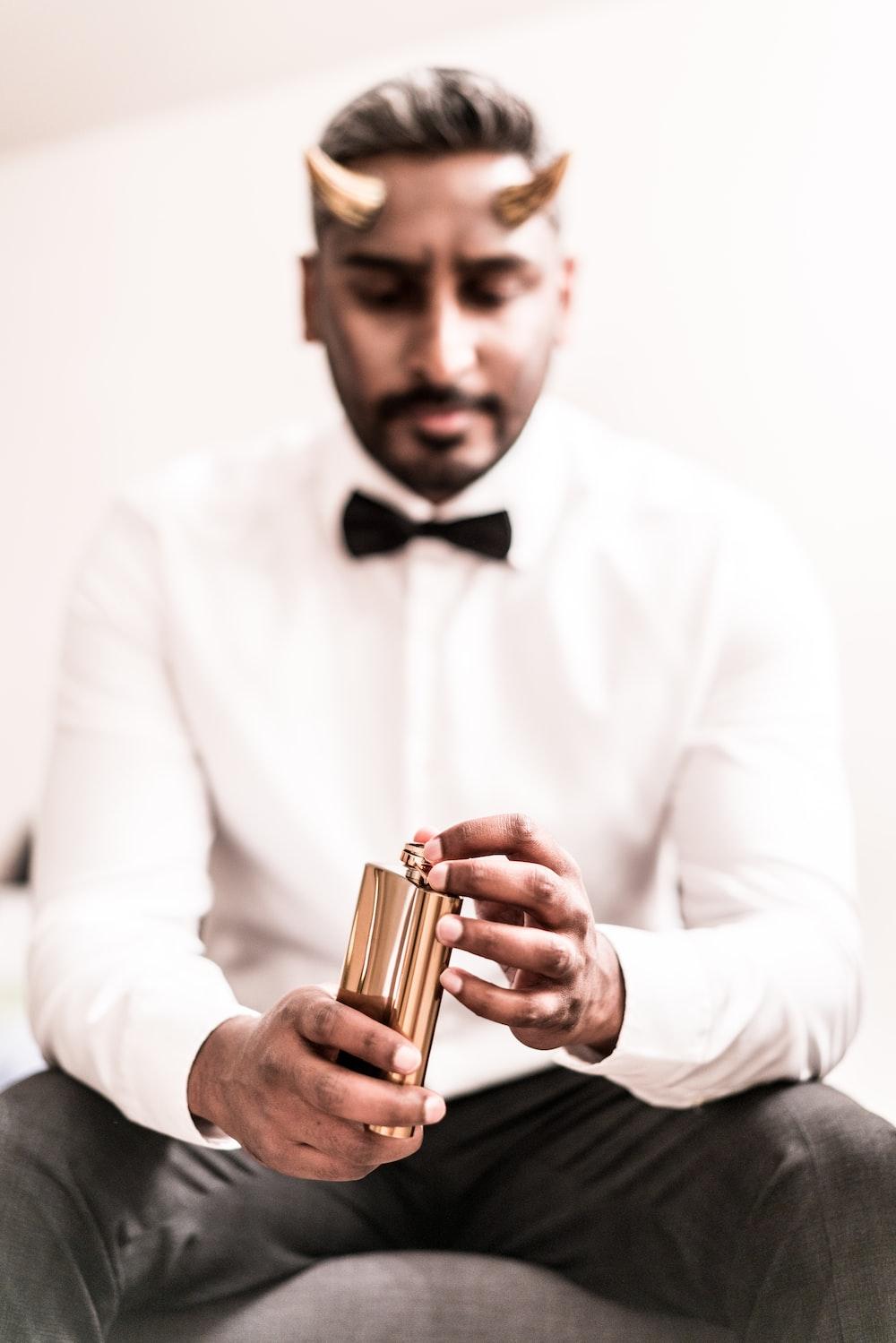 man in white dress shirt holding gold tube