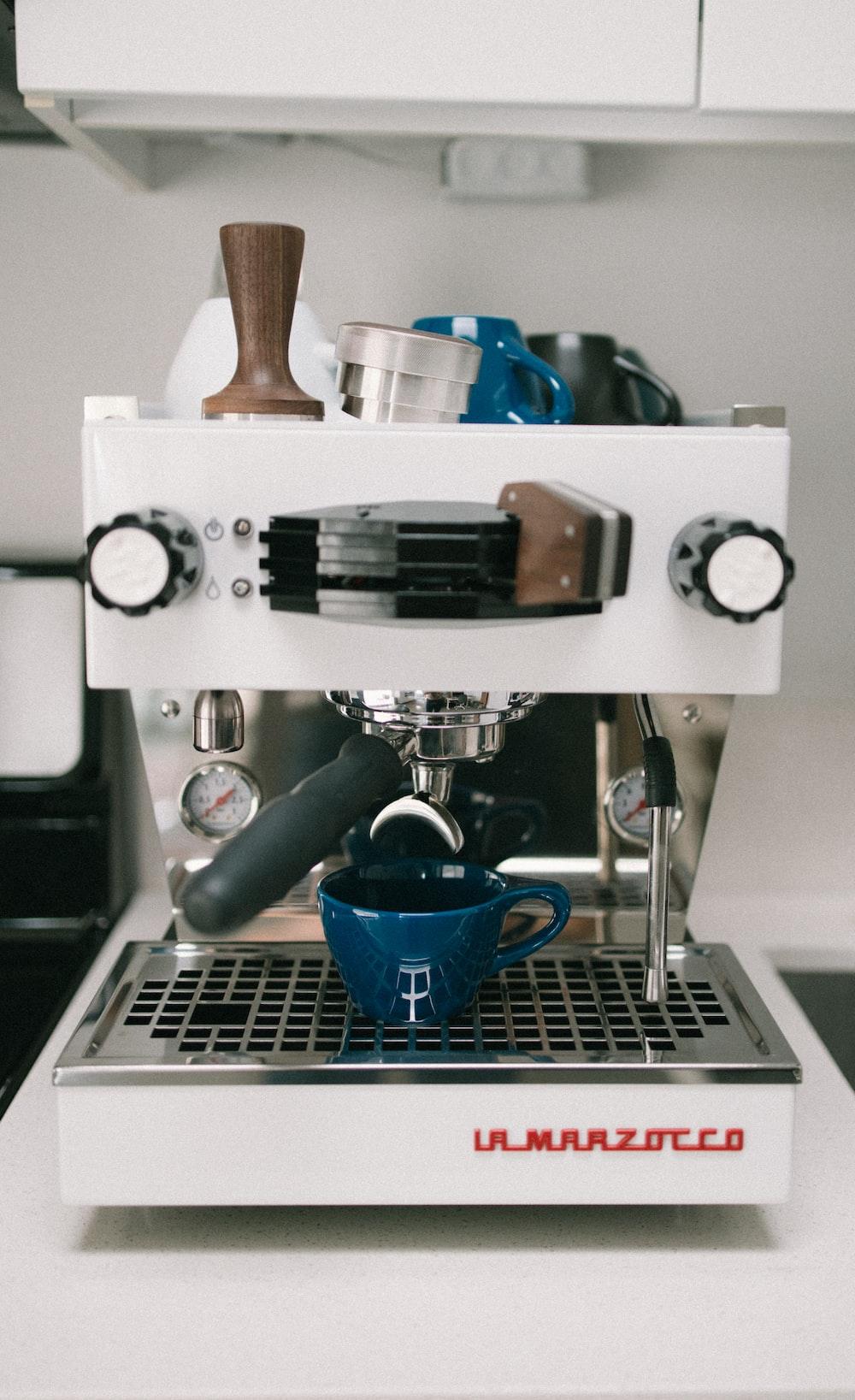 blue ceramic mug on silver and black coffee maker