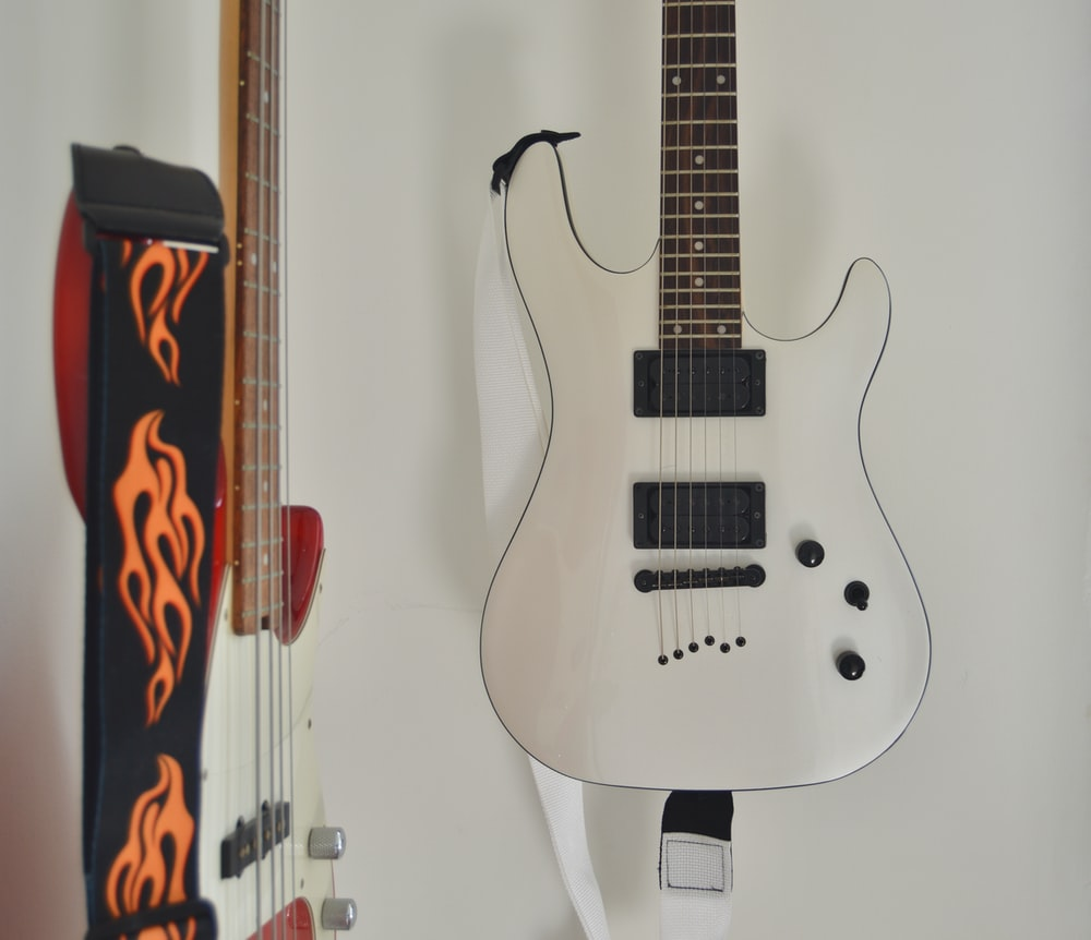 white and brown stratocaster electric guitar