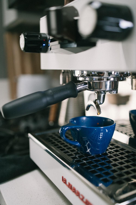 blue ceramic mug on black and silver coffee maker