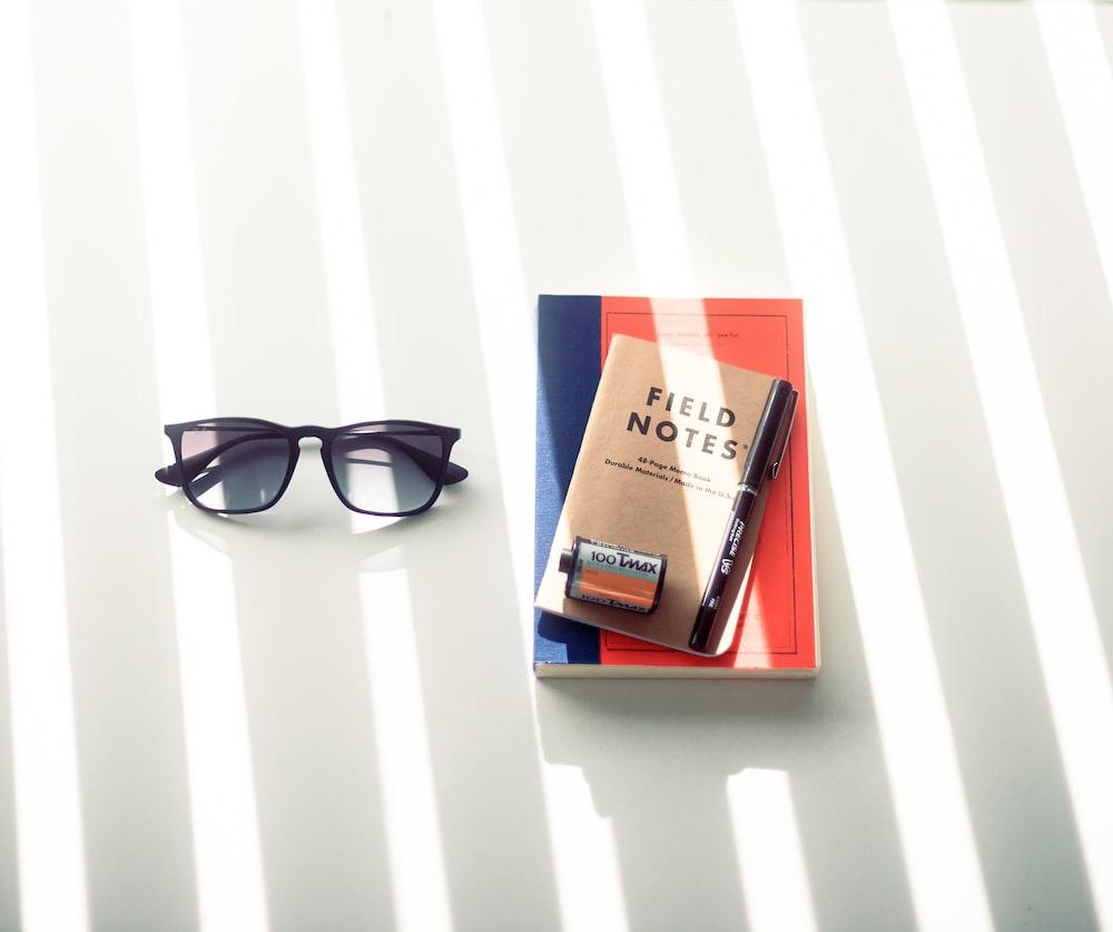 black framed sunglasses on white table