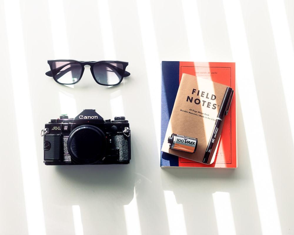 black nikon dslr camera beside black framed eyeglasses