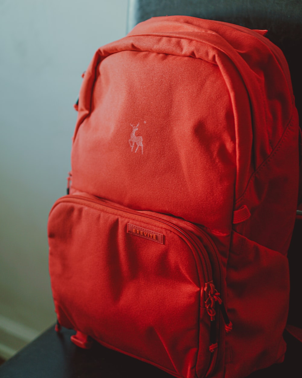 red and black backpack on white table