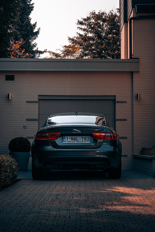 black bmw car parked beside white garage