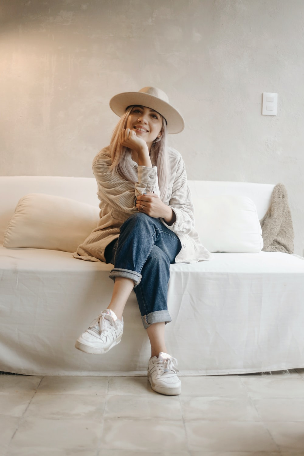 woman in white long sleeve shirt and blue denim jeans sitting on white couch