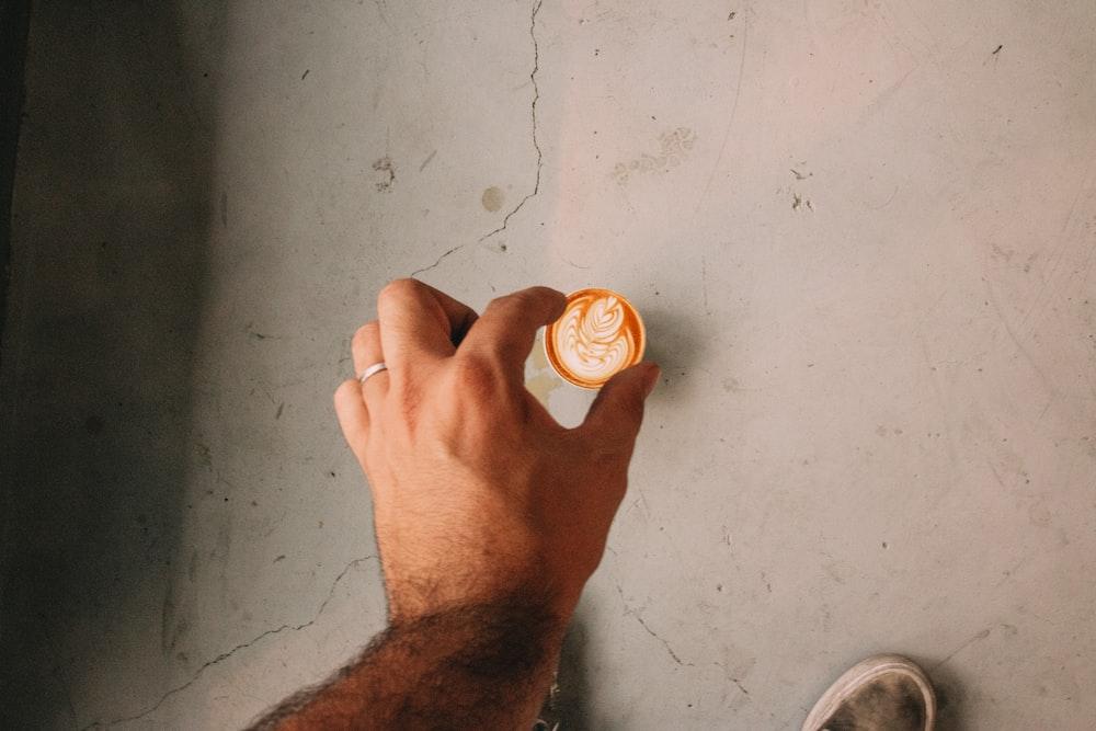 person holding white round plastic