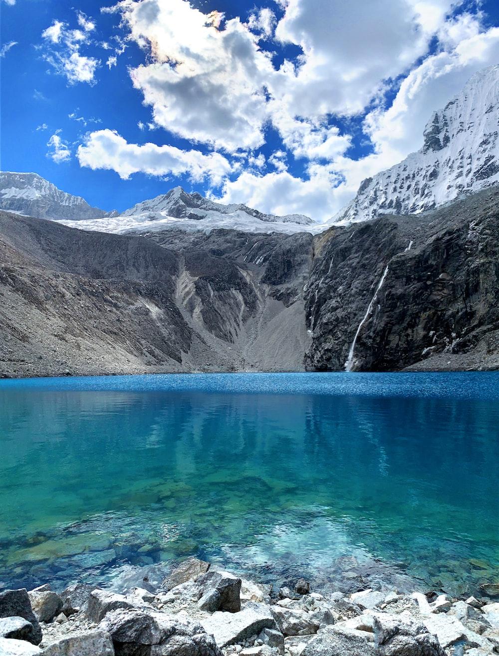 blue lake near gray mountain during daytime
