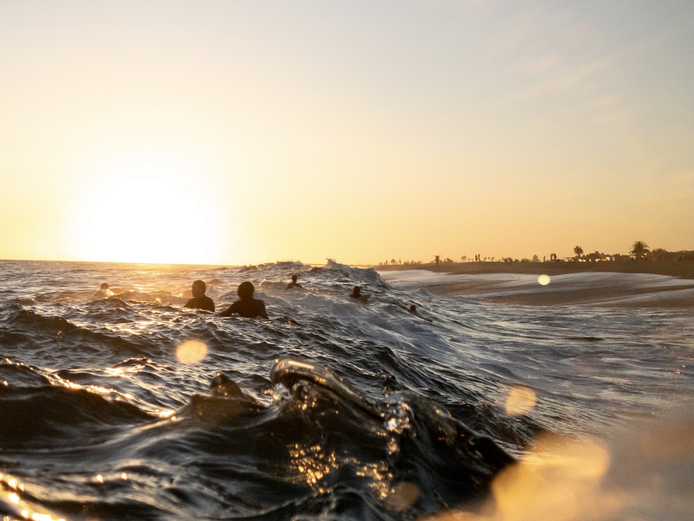 water waves on shore during sunset