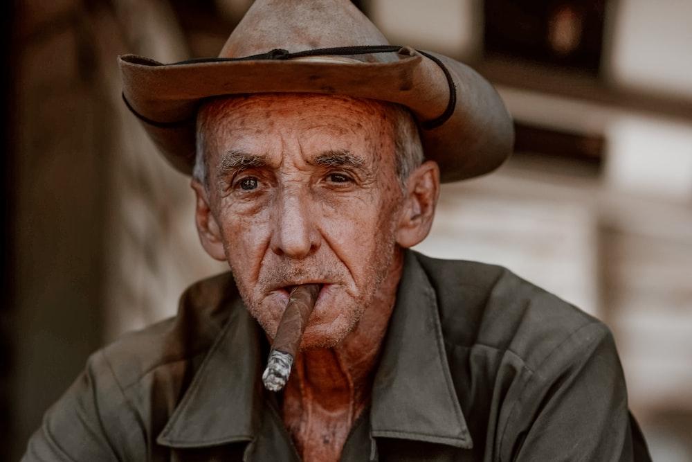 man in black leather jacket wearing brown cowboy hat