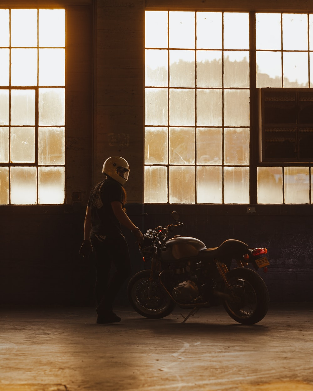 woman in black coat standing beside motorcycle