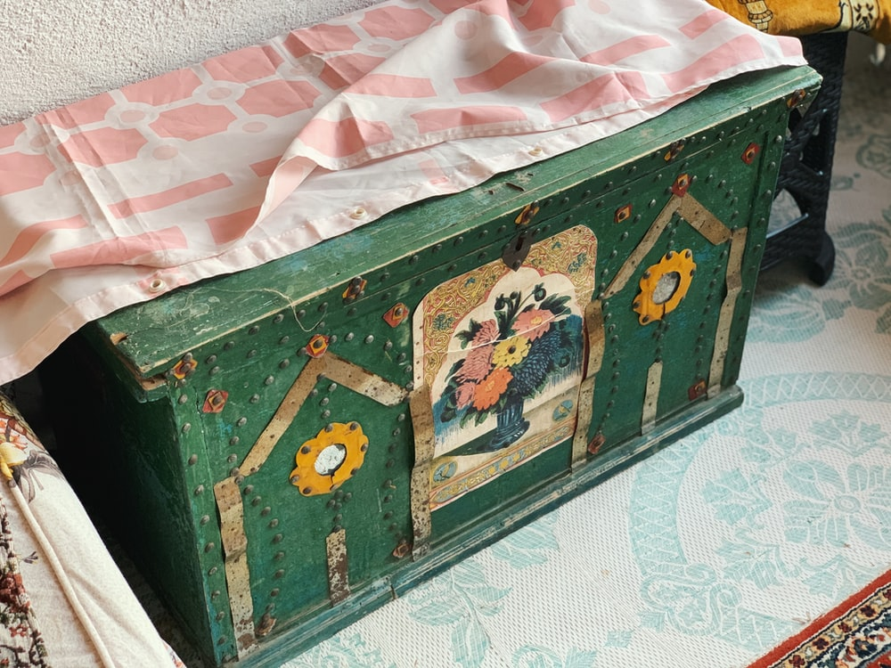 brown wooden chest box on white textile