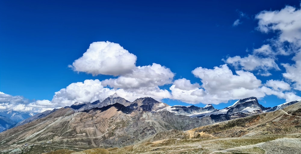 white clouds over brown and white mountains