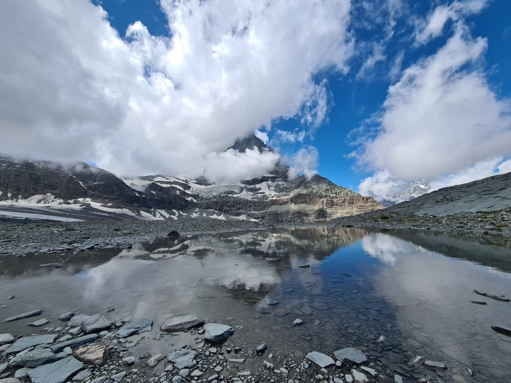 lake in the middle of mountains under white clouds and blue sky during daytime