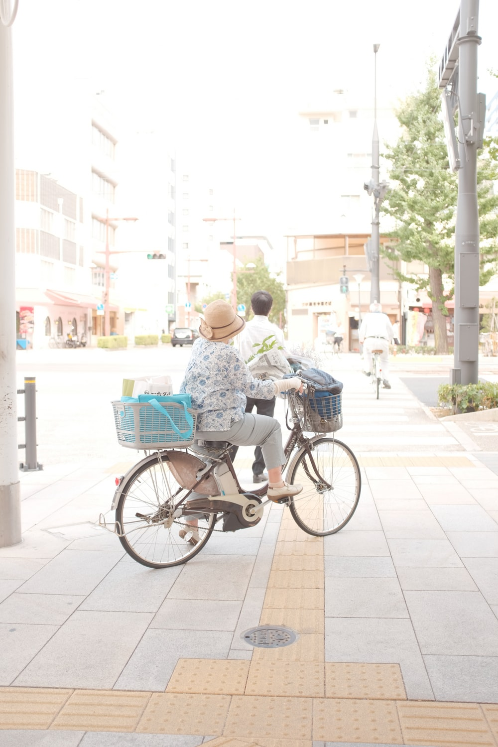 man in blue and white floral shirt riding on black city bicycle during daytime