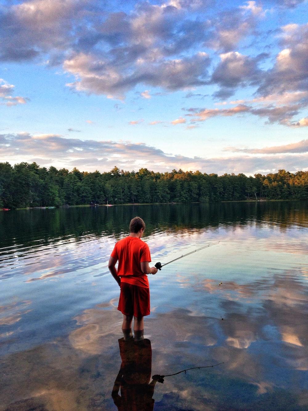 man in red shirt fishing on lake during daytime