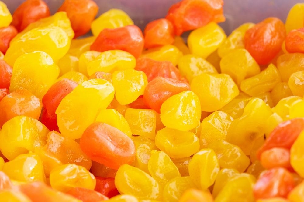 yellow and orange candies on blue plastic container