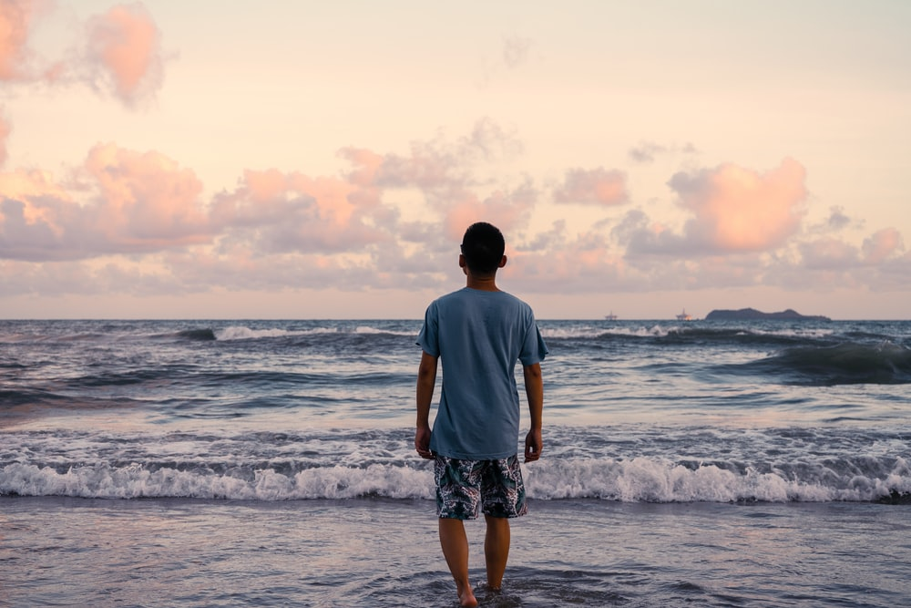 man in gray t-shirt standing on seashore during daytime