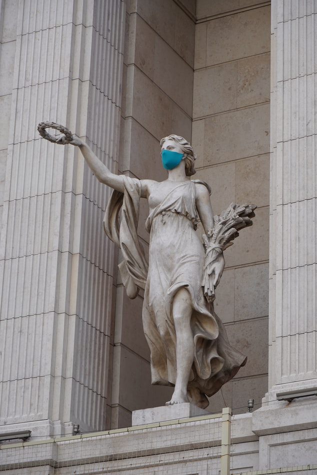 A photo of a stone statue in front of a stone wall. The statue appears to be a woman in a flowing dress, holding a bouquet of flowers in one hand and extending a laurel wreath in the other as if she's putting it on someone's head. She is wearing a medical face mask.