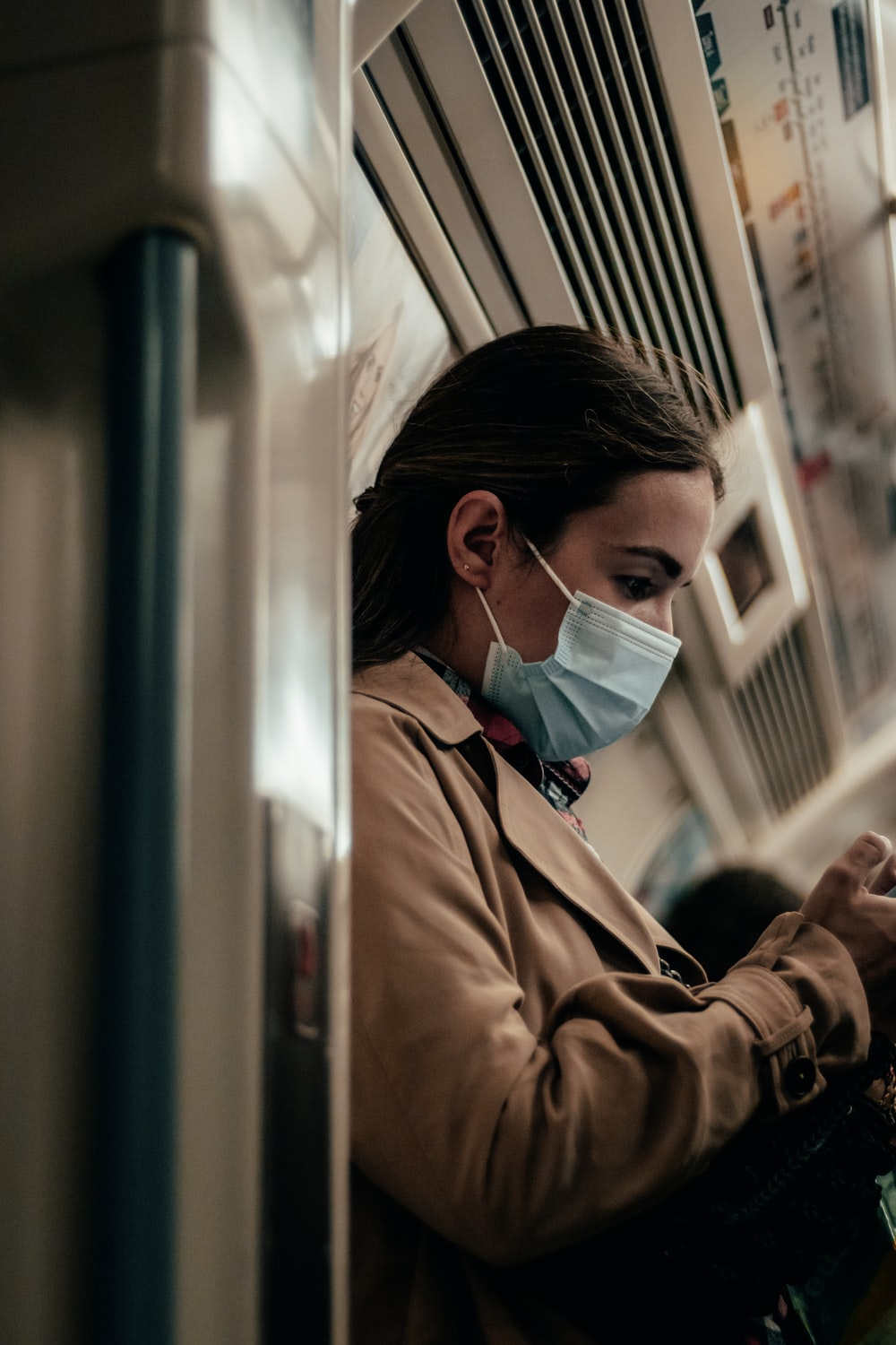 woman in brown coat wearing white mask