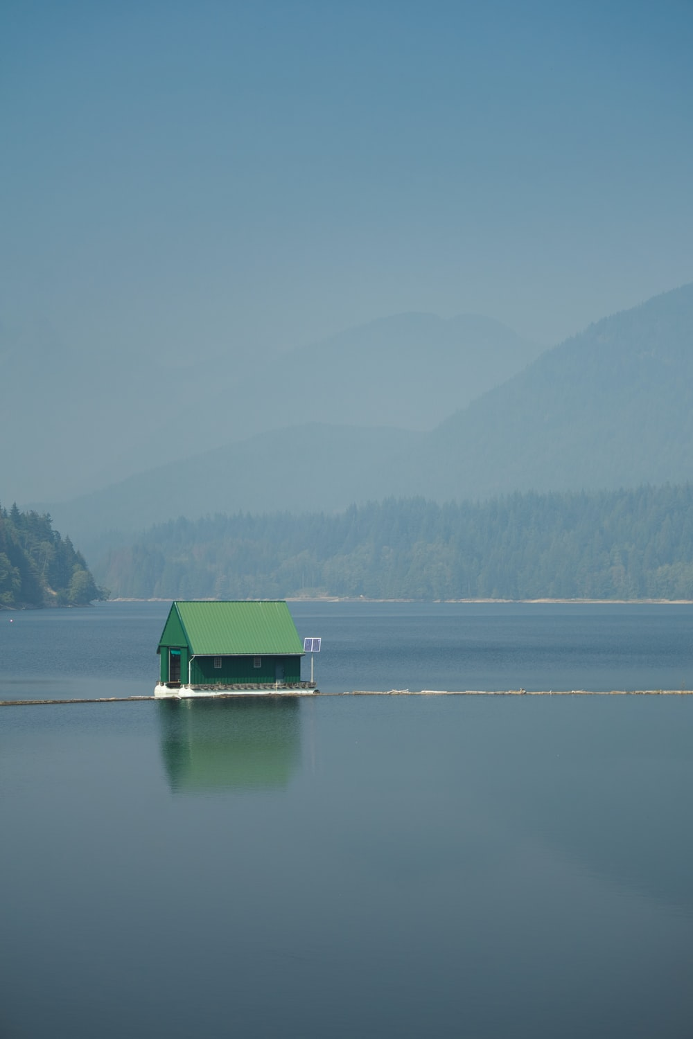 green and white house on lake during daytime