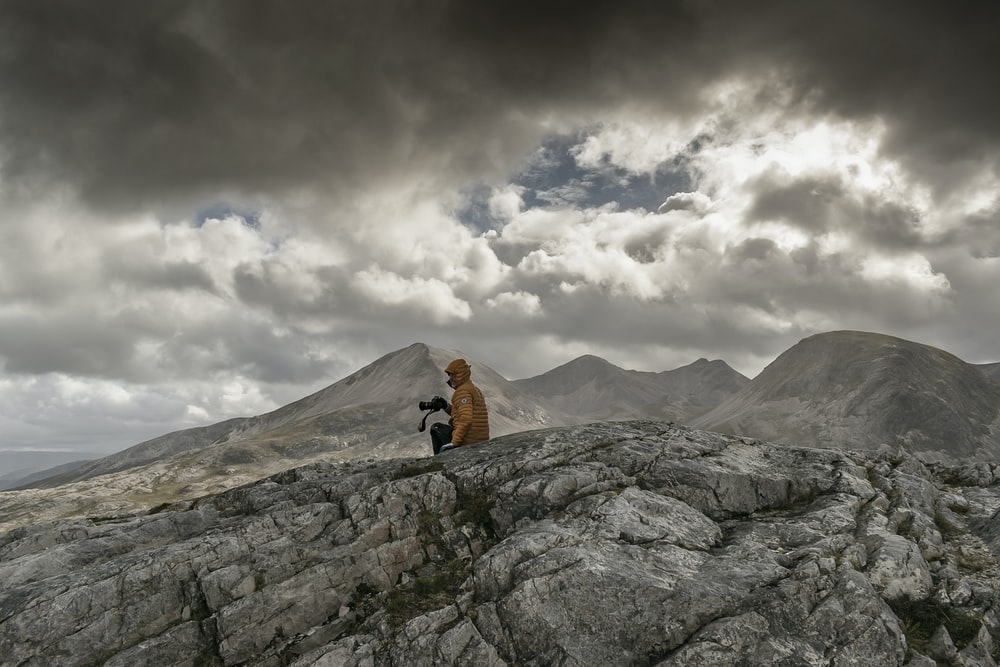 person in orange jacket sitting on rock mountain under white clouds during daytime