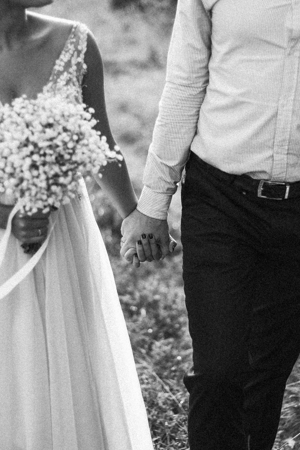 grayscale photo of man and woman holding bouquet of flowers