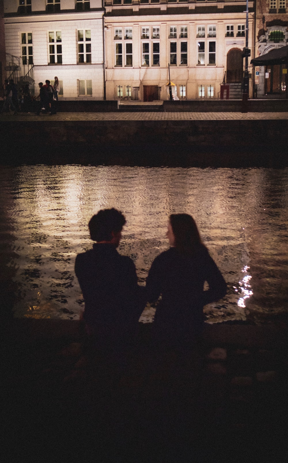 silhouette of man and woman standing beside body of water during night time
