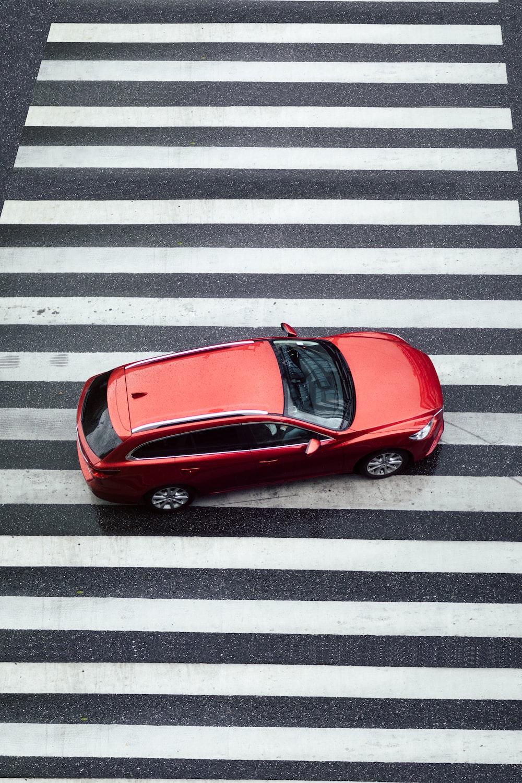 red car parked on pedestrian lane