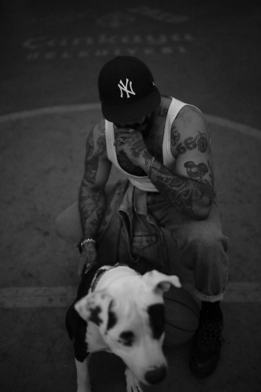 man in black hat holding white short coated dog