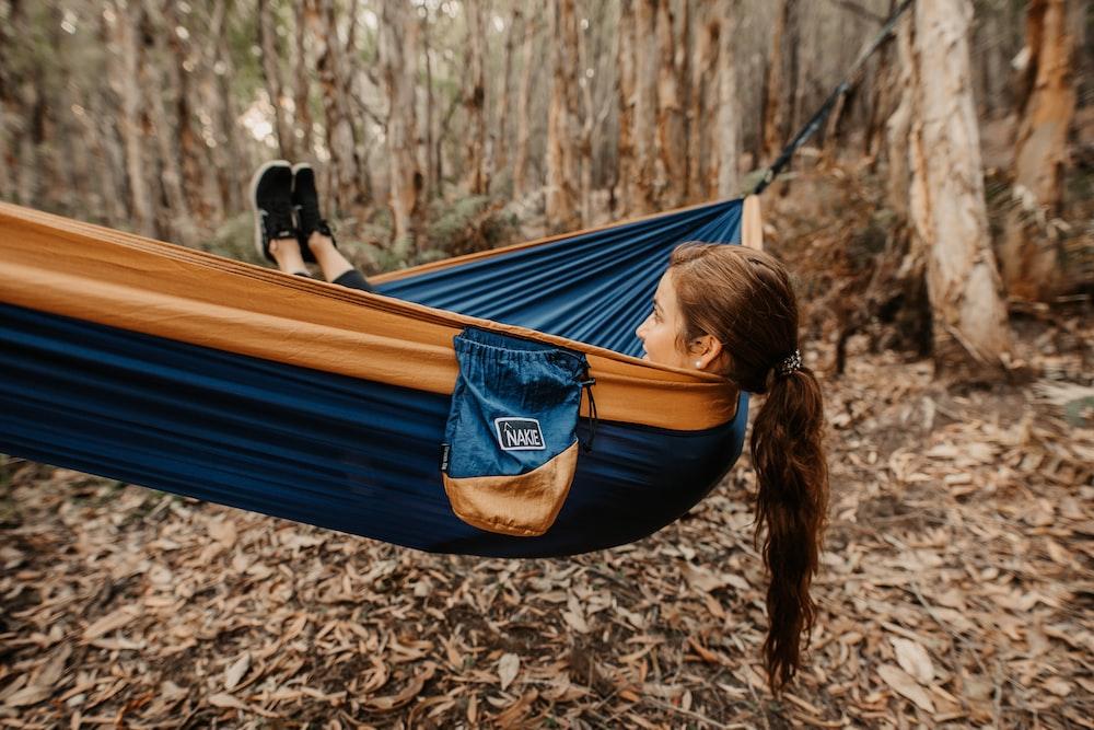 woman in black shirt lying on hammock