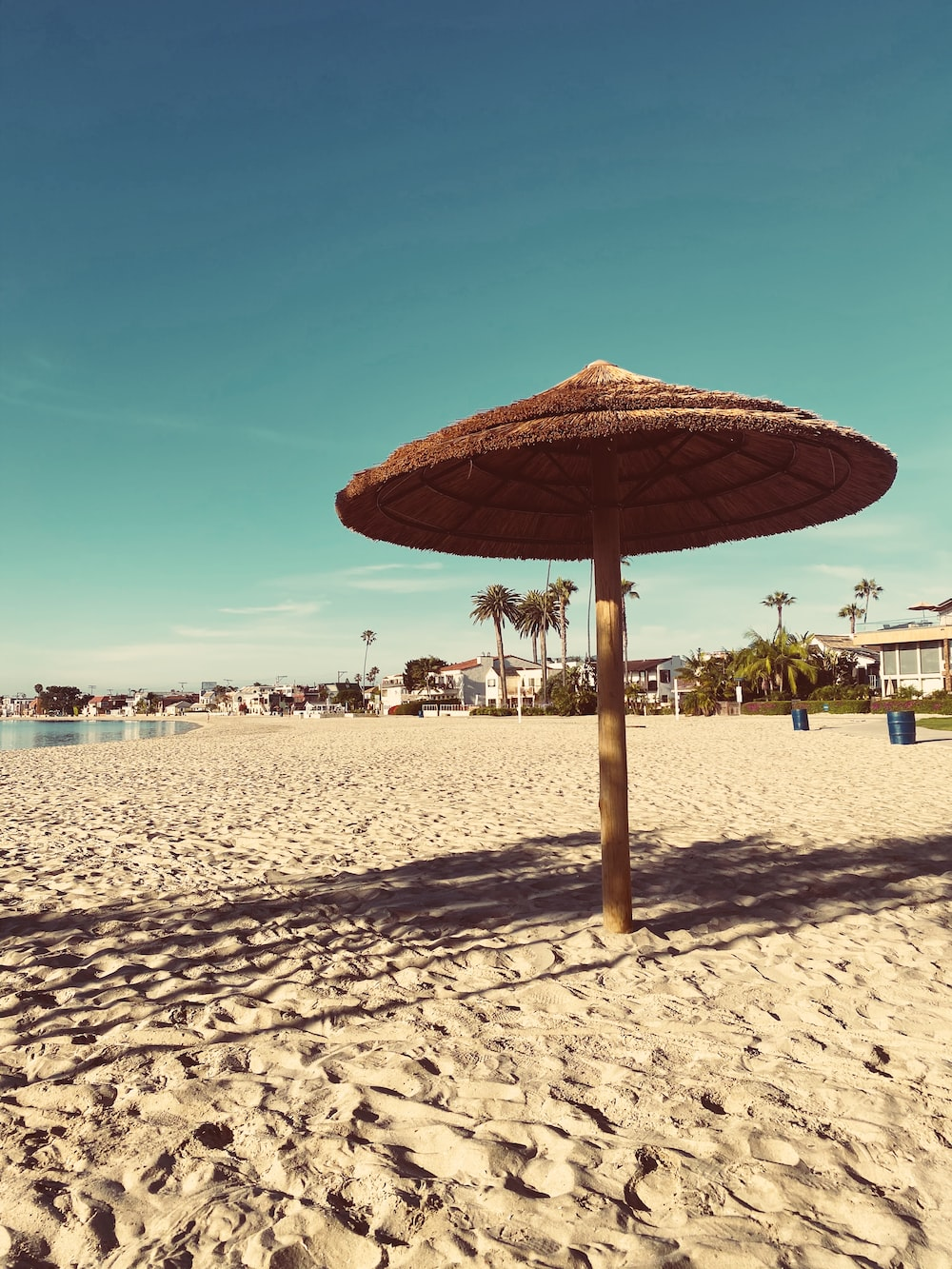 brown and white umbrella on beach during daytime