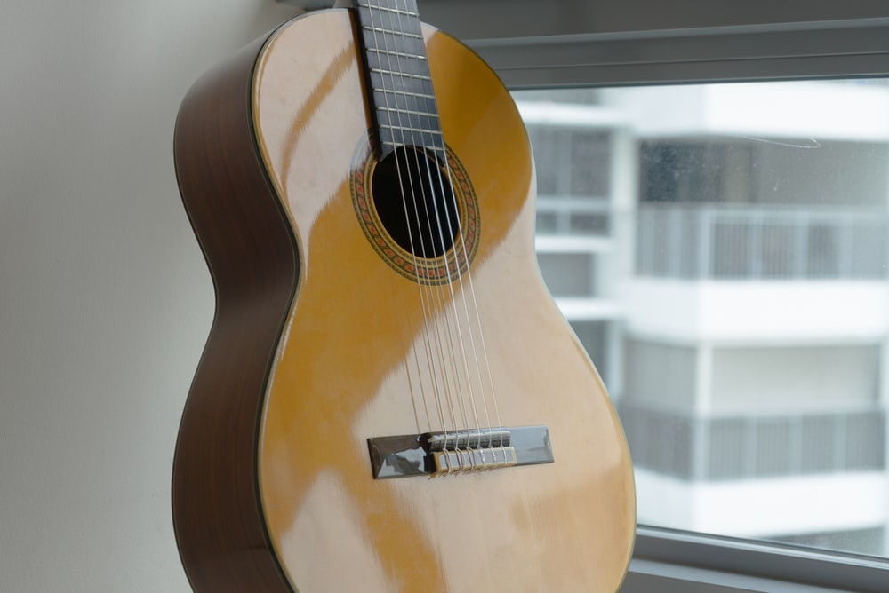 brown acoustic guitar on glass window